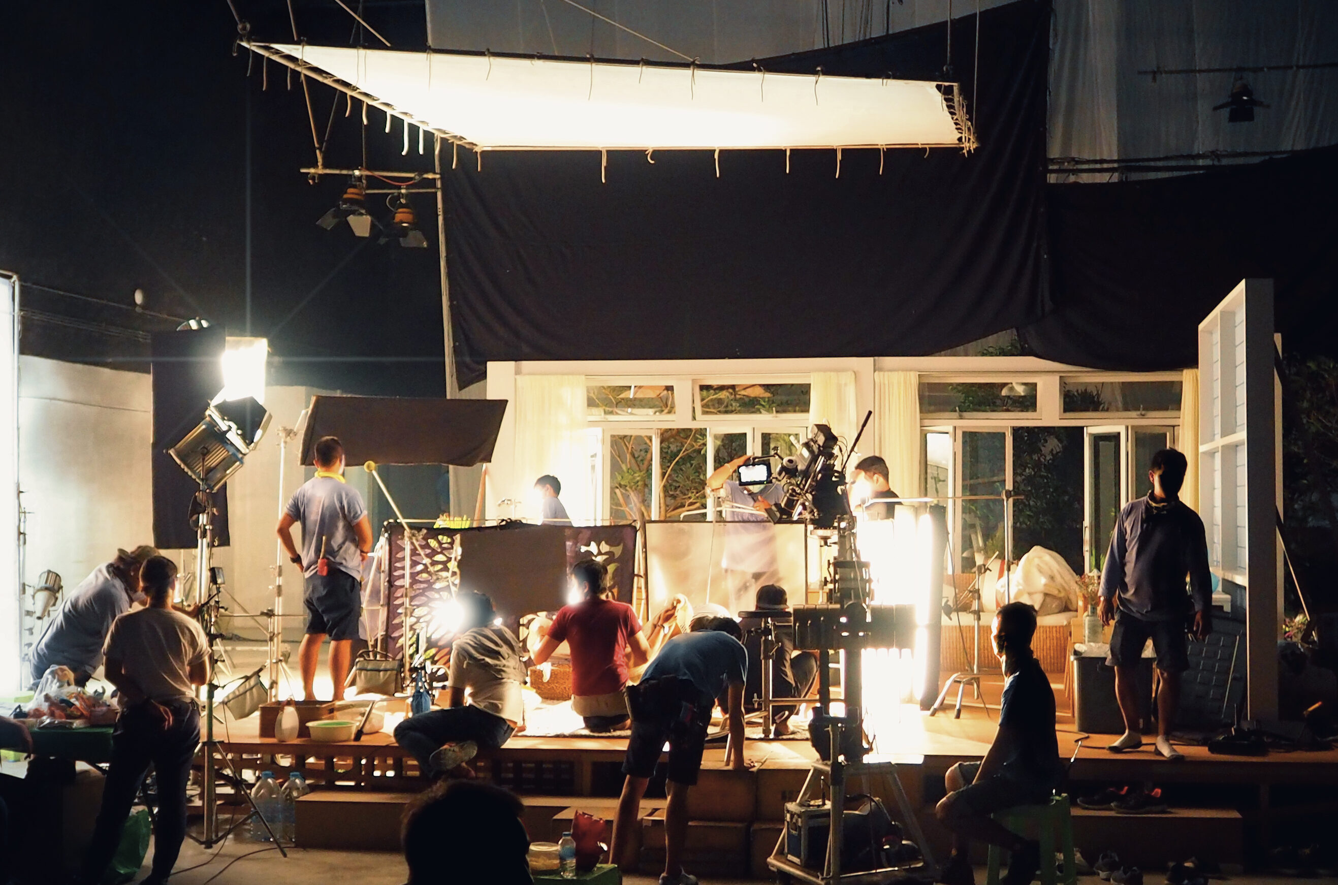 Silhouette of people working in big production studio for shooting or recording movie video by digital camera and lighting set.